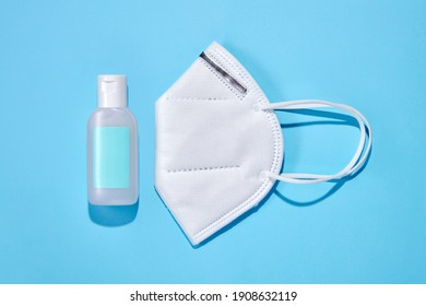 Top view of bottle with cleansing hand gel and protective FFP facial mask for coronavirus prevention placed on blue background