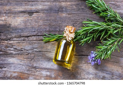 Top view Bottle glass of essential rosemary oil with rosemary branch and flower on wooden rustic background. herbal oil concept