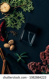 top view of bottle of perfume with aromatic spices and spruce branch on black