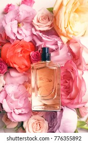 Top view of bottle with perfume on beautiful flowers
