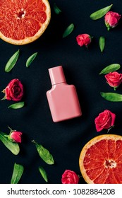 top view of bottle of perfume with rose buds and grapefruit slices around on black