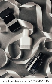 top view of bottled perfumes and white ribbons on grey