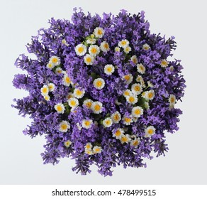 Top view of a bouquet of lavender and camomile flowers on a white background. Colorful summer bouquet of purple lavender and yellow chamomile flowers. Photo from above.