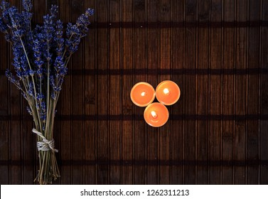 Top view of bouquet of lavender flowes and aroma candels on wooden background. Aromatherapy. Flat lay
