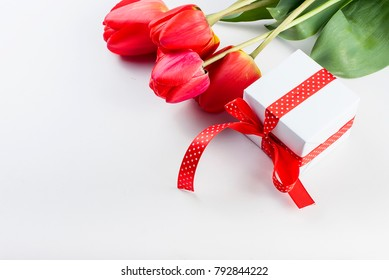 Top view  bouquet of red tulips and daffodils and gift box with red ribbon  on the white background.  flowers background concept  Copy space