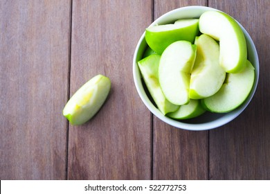 Top view of a bowl of apple slices on a wooden table.