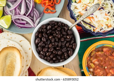 Top view of bowl with black beans, mini taco boats, cabbage, salsa - ingredients for taco with black beans and vegetables.