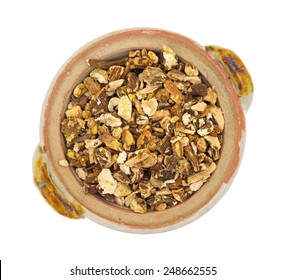 Top view of a bowl filled with dried dandelion root on a white background.
