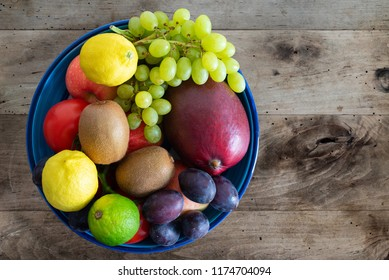 top view of bowl filled with fresh fruits on rustic wooden table
