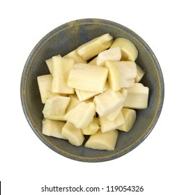 Top view of a bowl filled with pieces hearts of palm on a white background.