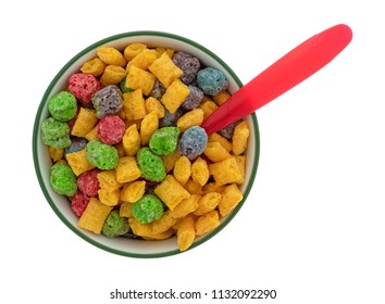 Top view of a bowl of generic fruit flavored breakfast cereal with a red plastic spoon in the food isolated on a white background.