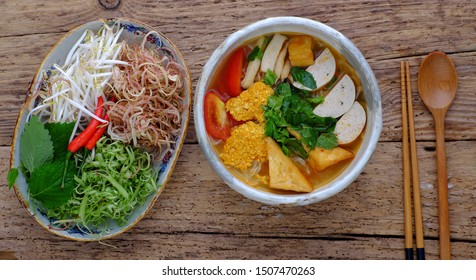 Top view bowl of homemade vegan rieu noodle soup or vegetarian crab paste vermicelli soup; a traditional Vietnamese dish; plate of vegetables; herbs; ready to eat on wooden background