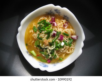 a top view for a bowl of instant noodles with spring onion dressing