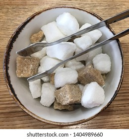 Top view of a bowl with pieces of white and brown sugar cubes and with sugar-tongs on a wooden table. Close up photo.