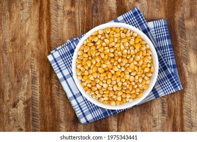 Top view of bowl with Popcorn Kernels Uncooked. Popcorn Kernels Uncooked in a Ceramic Bowl. The image is a cut out, isolated on a wood background, with a clipping path
