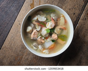 Top view bowl of Tom Yum Kung and Salmon on wooden table. Thai Spicy and Sour clear soup with shrimp and salmon.