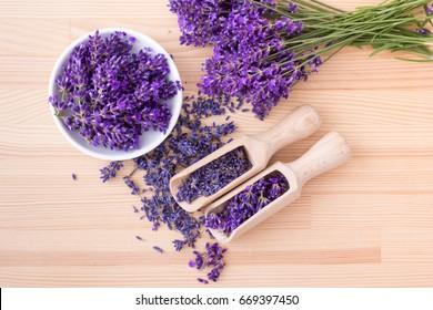 Draufsicht auf eine Schüssel mit Holzlöffeln mit getrockneten und frischen Lavendelblumen und einem Lavendel auf Holzhintergrund