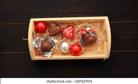 Top view of a box with chocolate candy balls and heart shapes. Inside a wooden box.  Some are opened with foil around them. On a black wooden background.