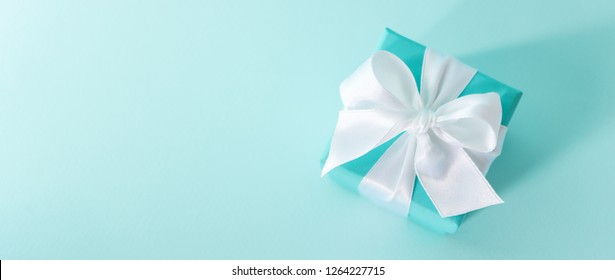 Top view of the box tied with silk ribbon on tiffany blue color pastel background. Gift festive selection. long wide banner with copy space