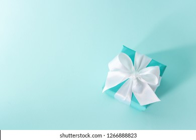 Top view of the box tied with silk ribbon on tiffany blue color pastel background. Gift festive selection.