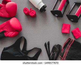 top view of boxing gym concept with boxing glove, Gym Outfit, skipping rope and accessories on yoga mat background.