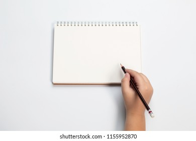 Top view of boy hand hold the pencil writing on blank white paper notebook mockup on  white isolated background / back to school concept