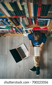 Top view, boy reading a opened book in library. Boy leaning against multi colored bookshelf in library, keeping a book in his hands and reading with laptop near. Education, Knowledge, Lecture.