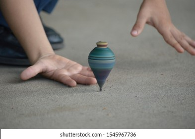 Top view of a boy's hands trying to catch a spinning top while spinning at high speed. Horizontal image