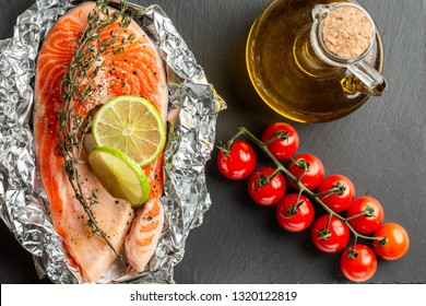 Top view of the branch of tomatoes and bottle of oil placed on black slate surface near the raw red fish slice in foil