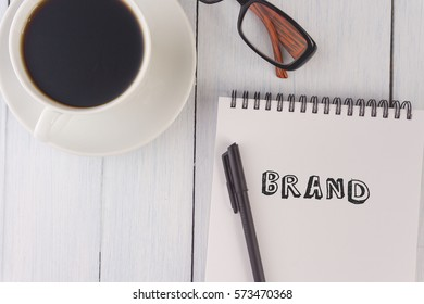 top view of brand written on notebook,pen,coffee,glasses on the white desk