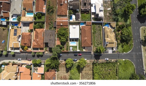 Top view of a brazilian city with roofs, swimming pool and cars parked