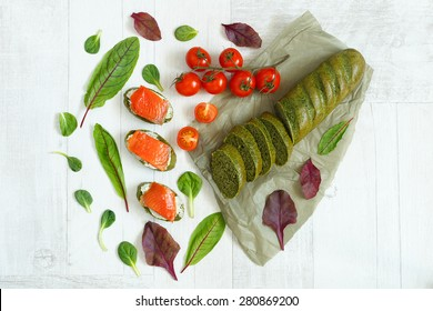 top view of a bread with spinach, salmon, herbs and cherry tomatoes