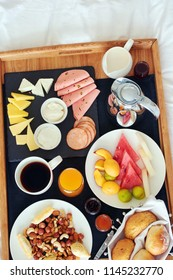 Top view of breakfast in bed in Azerbaijan hotel: fresh fruit, cheese and cold cut platter, nuts and pastry, bread basket, coffee with milk and juice.