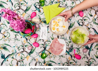 Top view of breakfast table with Easter meal and woman hand, fried eggs, salad, hams, lilac flower. Spring holiday decoration.