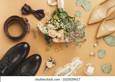 Top view of bride and groom shoes, floral corsage, bouquet, golden rings. Preparation for wedding concept, copy space