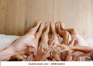 Top view of bridesmaids and bride sitting on bed and toasting champagne. Celebrating a bachelorette party at home.