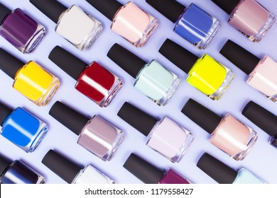 top view of bright bottles with gel-lacquer on a lilac background. Multicolored varnishes for the covering of nails, manicure and pedicure. Nail work flat lay concept. Stylish trendy female manicure