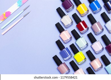 top view of bright bottles with gel-varnish for covering nails, nail files and a brush on a lilac background with space for text. Nail work flat lay concept. Stylish trendy female manicure.