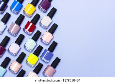 top view of bright bottles with gel-varnish for covering nails on a lilac background with space for text. Nail work flat lay concept. Stylish trendy female manicure.