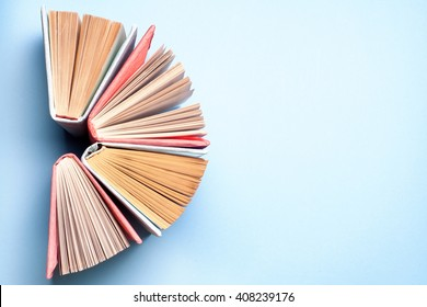 Top view of bright colorful hardback books in a circle. Open book, fanned pages.   Education essential for self improvement, gaining knowledge and success in our careers, business and personal lives.