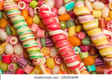 top view of bright delicious multicolored caramel candies and swirl lollipops on wooden sticks