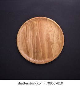 Top view bright empty wooden dish/bowl on black stone board background