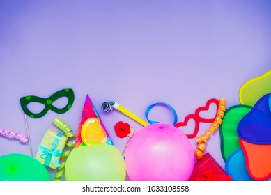 Top view bright party tools and decoration - baloons, funny carnival masks, festive tinsel on lilac background. Happy birthday greeting card. Purim. Design concept. Select focus, place for text.