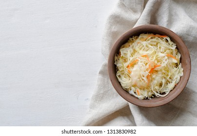 Top view of brown ceramic bowl of sauerkraut with chopped cabbage and carrot on grey towel sitting on white table surface