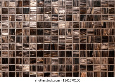 Top view of brown glass mosaic wall surface. Finishing material. Abstract architecture / interior background with checkered geometric structure.