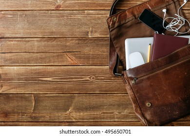Top view of brown leather bag with laptop, cell phone, notebook and pen inside on wooden background. Copyspace.