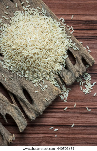 top view brown rice pile on a dark wooden table