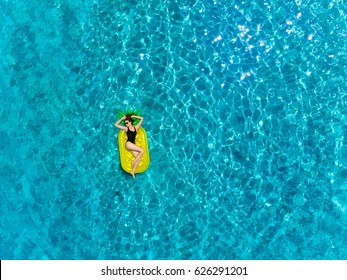 Top view of brunette woman swimming on the inflatable big pineapple in the transparent blue sea. Aerial view of lady relaxing on the floating mattress.