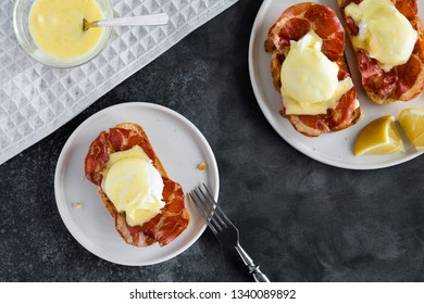 Top view of bruschetta with parma ham and Egg Benedict. Classic Eggs Benedict with bacon, hollandaise sauce, view from above