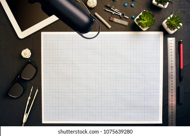 Top view of the builder's workplace, ruler, paper for drawings, compasses, glasses, tablet